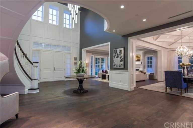 A grand spacious foyer with a center table over hardwood flooring. It has a huge white front door framed with glass panels that complements the elegant staircase.