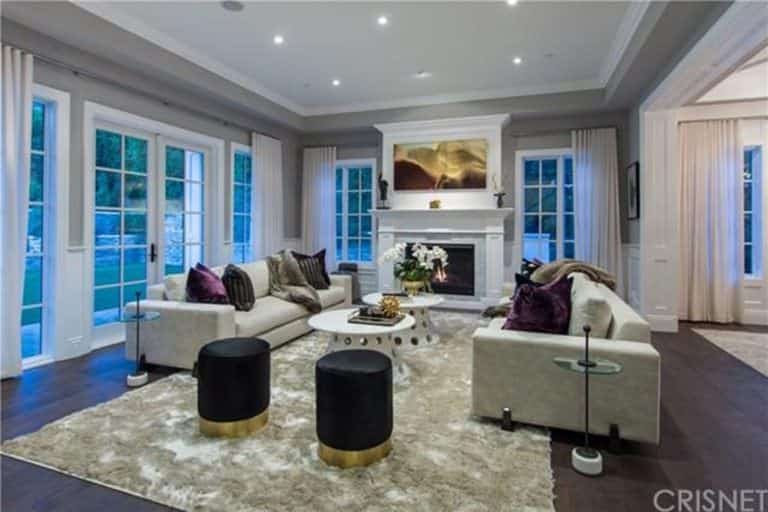 A stylish living room featuring cozy seats and a large fireplace under the attractive tray ceiling with gray accent.