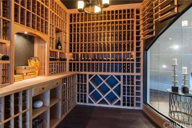 A deluxe temperature-controlled wine room with custom built-in shelves and racks against a black wall. It includes a glass door and iron wrought chandelier.