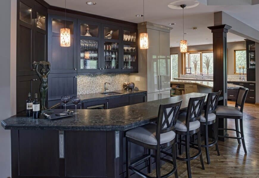 Traditional home bar with dark hardwood built-in cabinets and marble counter along with pendant lights and recessed ceiling lights.