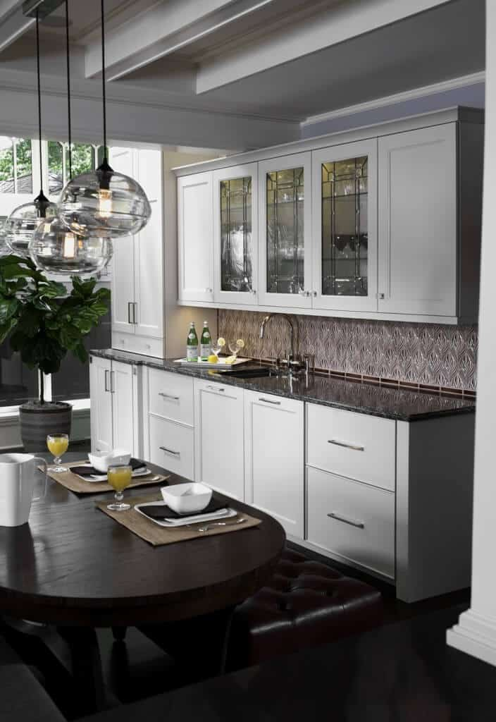 Traditional home bar with white cabinets and ceiling along with oval-shaped table and pendant ceiling lights.