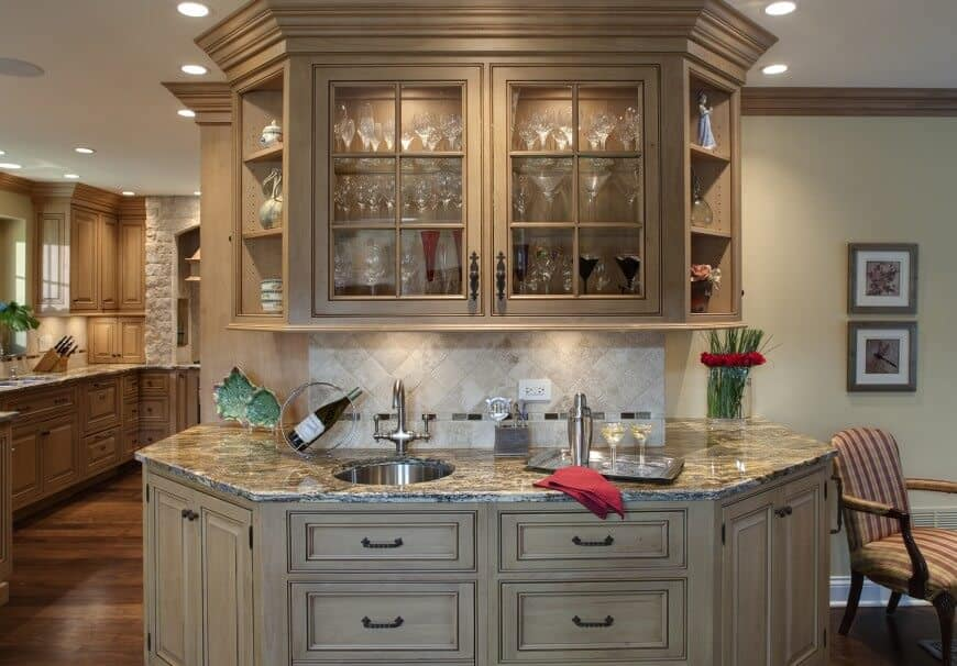 Traditional home bar with beige colored cabinet and shelving along with marble counter and single sink.