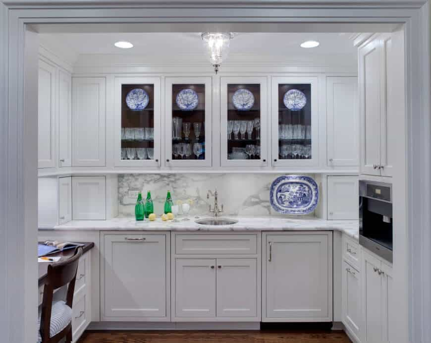 Traditional pure white home bar with hardwood flooring and marble counter with single sink.