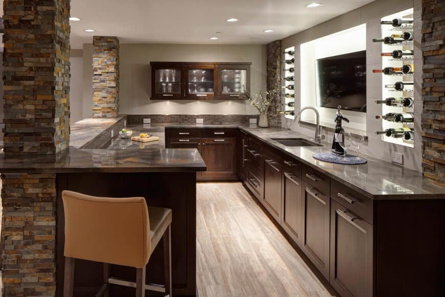 Modern home bar with a huge TV on screen and hardwood flooring.