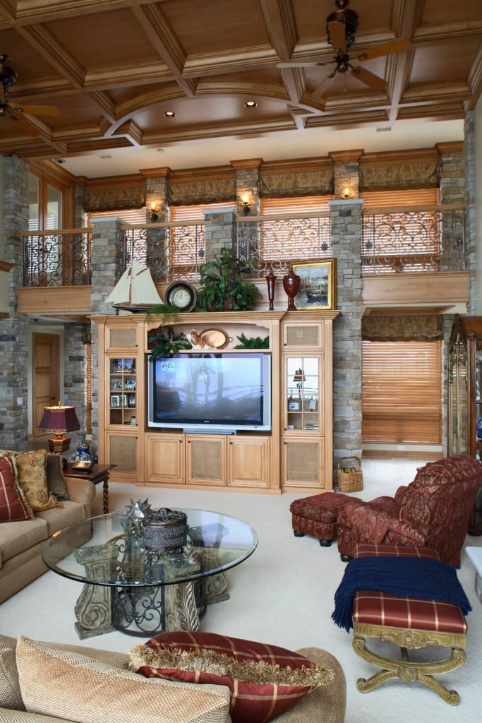 A round glass top coffee table faces the television on a wooden cabinet fixed to the stone brick columns in this living room with a high wooden coffered ceiling.