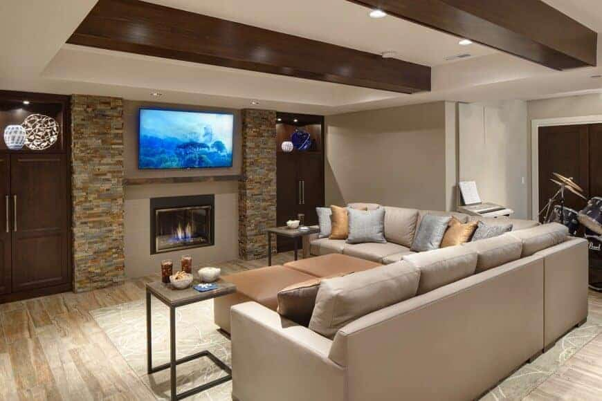 A formal living space set in the home's finished basement. The room offers a fireplace, a TV on the wall and a drum set on the side.