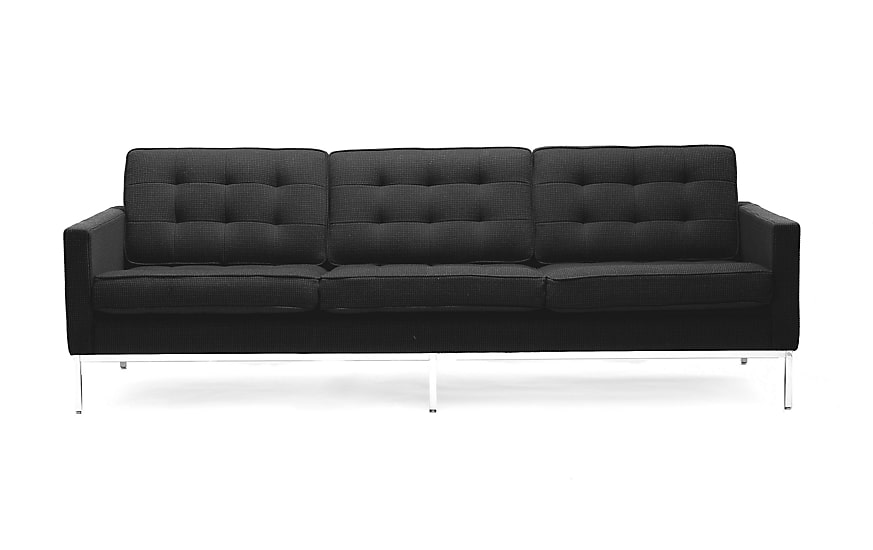 Three-seater sofa in black upholstery, tufted back cushions, and steel legs.