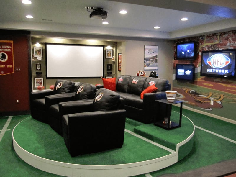 Quintessential sports themed man cave with rotating stadium seating plush chairs facing huge projector style TV screen. In fact, there are multiple TVs throughout the space along with all kinds sports memorabilia on the walls. This is a sports lovers man cave.