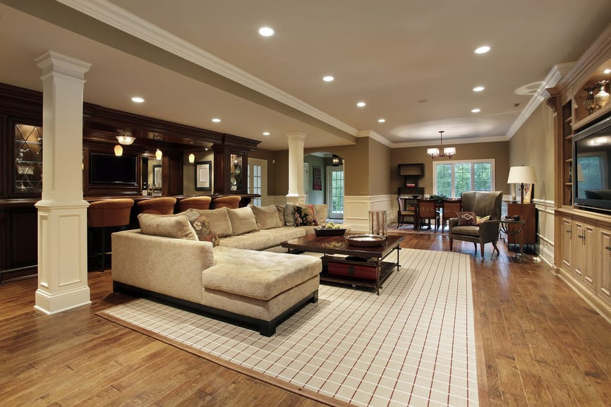 Large man cave boasting an elegant bar set up and a cozy sofa set on top of the gorgeous hardwood flooring topped by a stylish rug.