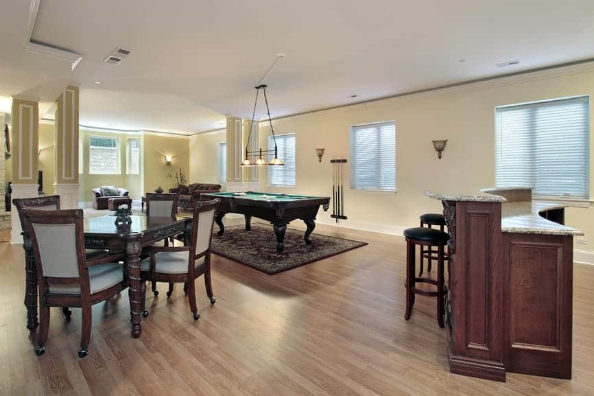 This home features a man cave with hardwood flooring and beige walls. The room also features a small bar area and a billiards pool lighted by a charming pendant lighting.