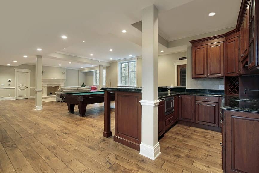 This bar features black granite countertops. There's a billiards pool and a living space, both set on the hardwood flooring.