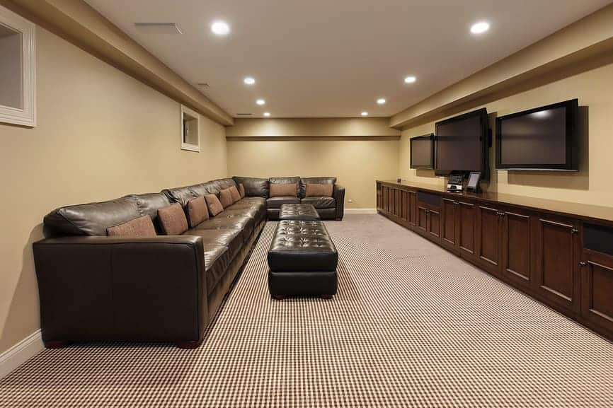 Large home theater featuring black elegant sofa set with beige walls and classy carpet flooring.