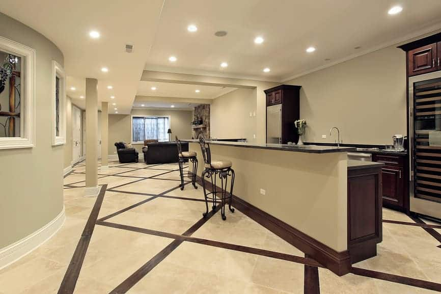 A modern and classy basement with a living space and a large bar area lighted by recessed lights. The flooring looks so stunning.