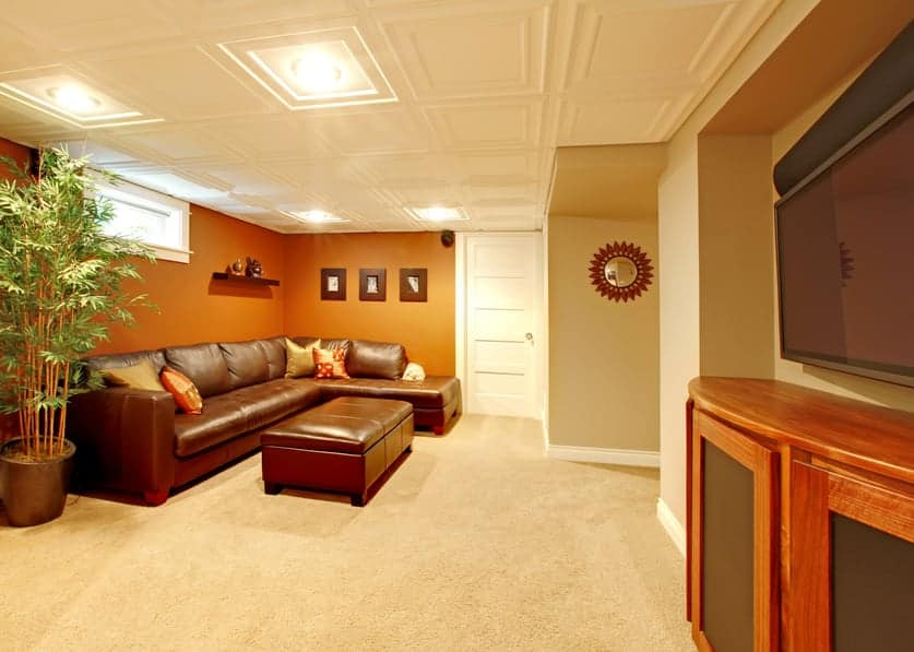 A living room set up in the home's basement, featuring leather seats set on the carpet flooring. The ceiling looks magnificent as well.