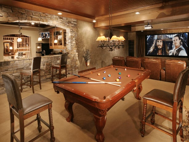 A glamorous man cave featuring a home theater area with sectional seats along with a billiards table lighted by a gorgeous chandelier. There's a bar area as well.