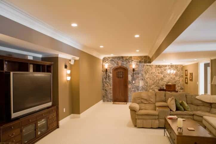 This home features a man cave boasting a cozy sofa set surrounded by brown walls and a stunning ceiling.