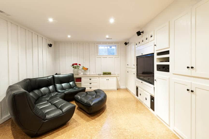 A small basement turned media room with black elegant theater seats set on the classy floors.