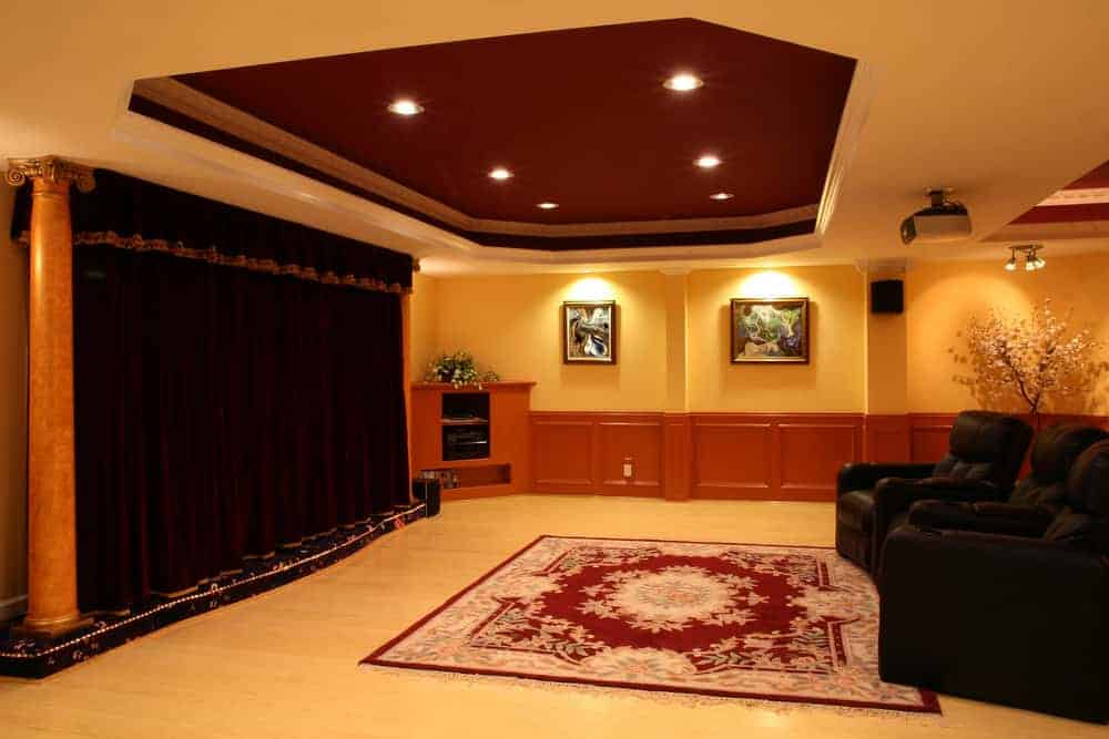 A majestic home theater with black curtain matching the black theater seats in front. The tray ceiling adds elegance to the room.