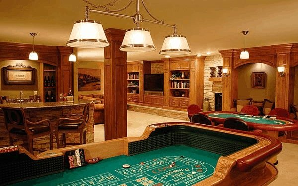 A large finished basement with a living space, a gambling table set and a bar area. The room features carpet flooring and a regular ceiling.