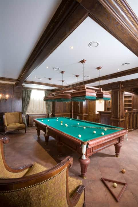 A close up look at this man cave's billiards pool set lighted by an elegant set of ceiling lights.