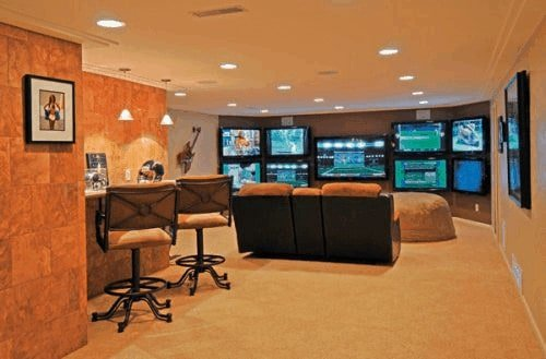 A basement turned into a game room with multiple monitors and a small bar area set on the carpet flooring and lighted by recessed ceiling lights.