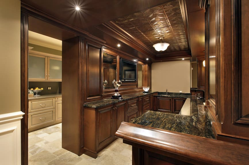 This bar features an elegant ceiling lighted by recessed and pendant lighting. The countertops are absolutely stunning.