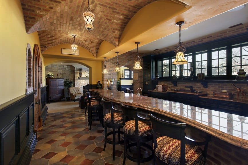 This man cave features a large long bar area with class countertop and bar stools lighted by glamorous pendant lights set on the stunning groin vault ceiling.