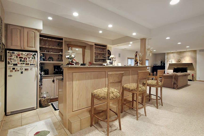 Large man cave featuring a rustic bar set up with classy bar stools set on the carpet flooring.