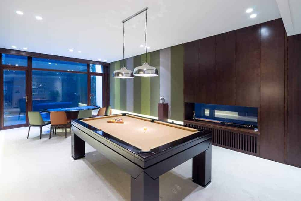 A game room with a billiards pool and a cards table set on the white carpet flooring and lighted by recessed and pendant lights.