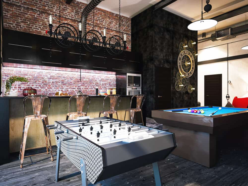 This game room boasts elegant black walls and wall decor along with the black hardwood flooring that looks very stylish.