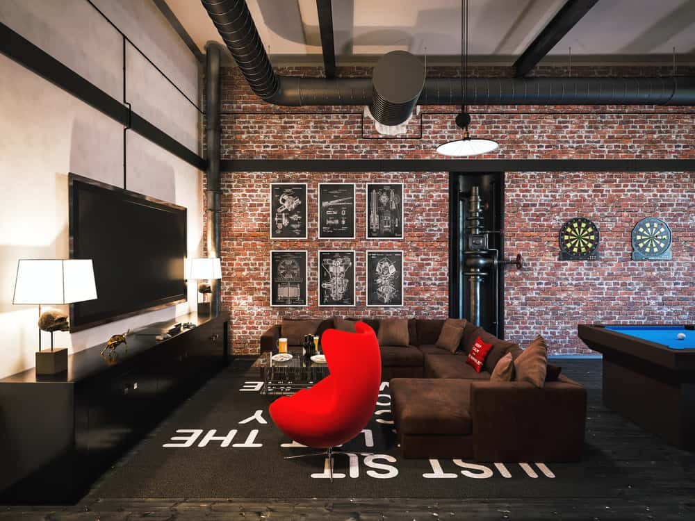 This very stylish game room features a brown sofa set in front of a widescreen TV and is set on the black rug on top of the hardwood flooring. There's a modern billiards pool on the back as well.