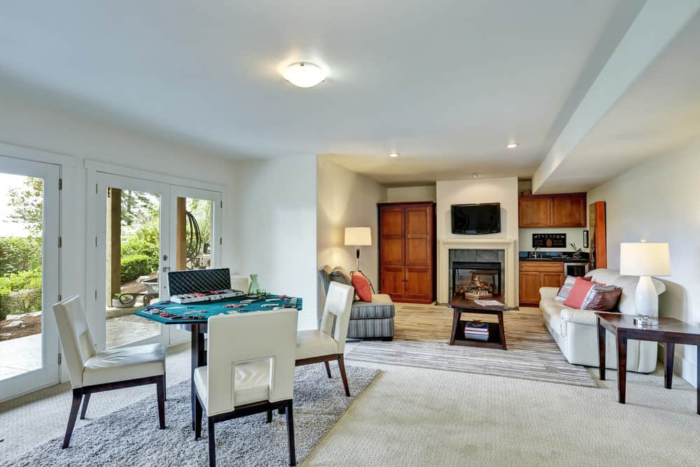 A simple white man cave featuring carpet flooring and classy rugs. The living space features a cozy sofa set along with a fireplace.