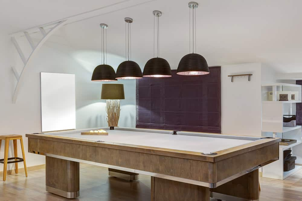 A close up look at this game room's modish billiards pool lighted by stylish pendant lights.