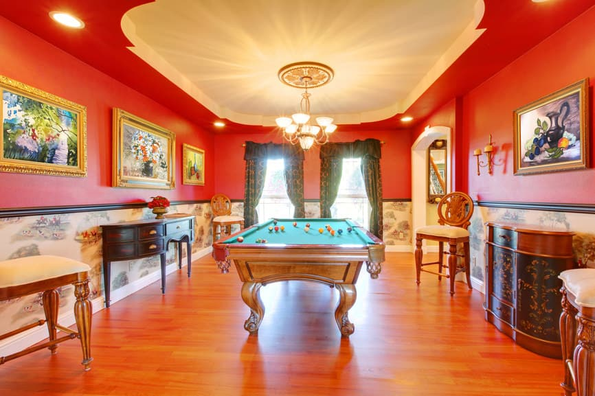 The red walls and tray ceiling lighted by a modern chandelier make this game room look tantalizing.