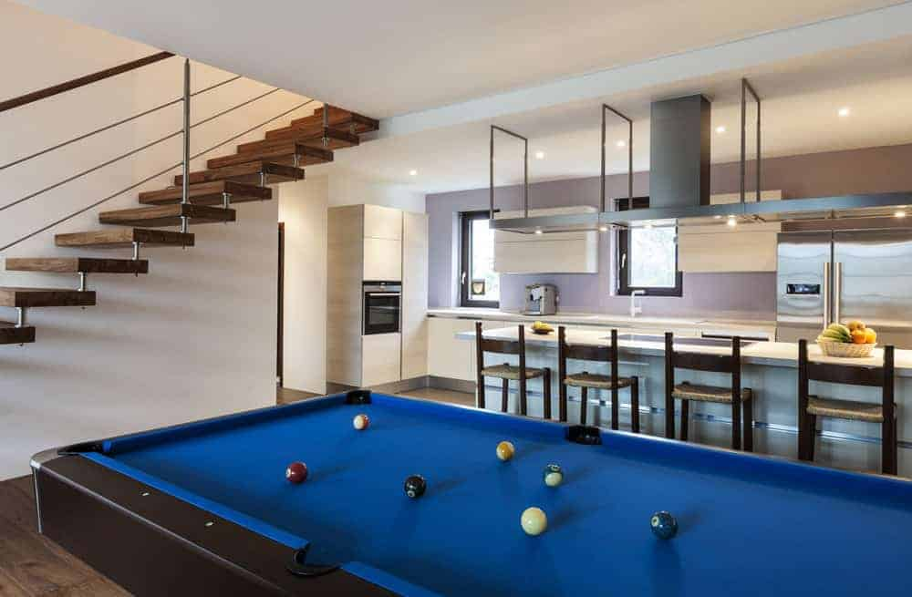 This modern home features a man cave with a very stylish billiards pool set on the hardwood flooring, along with a bar area with a smooth counter.