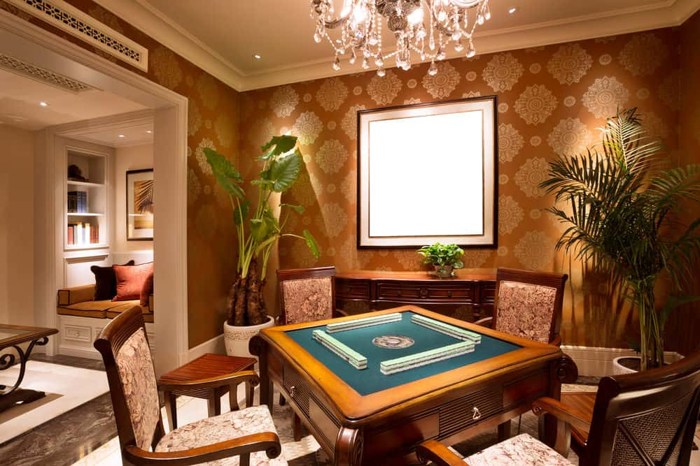 Vegas style man cave with elegant card table illuminated by a chandelier. The adjacent space features the tiniest home library ever - a nook with built-in cushioned seating flanked by small book shelves. This man cave is an example that has wallpaper instead of the usual paint or wood paneling.