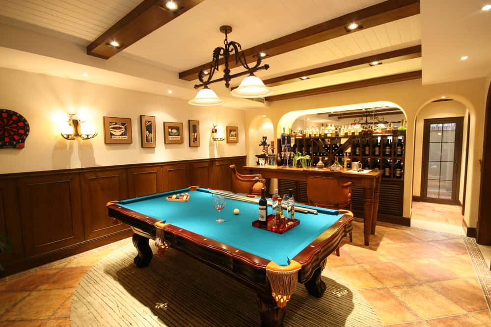 This man cave features a classy bar area with stylish wine cellar and a billiards pool set on the rug on top of the tiles flooring.