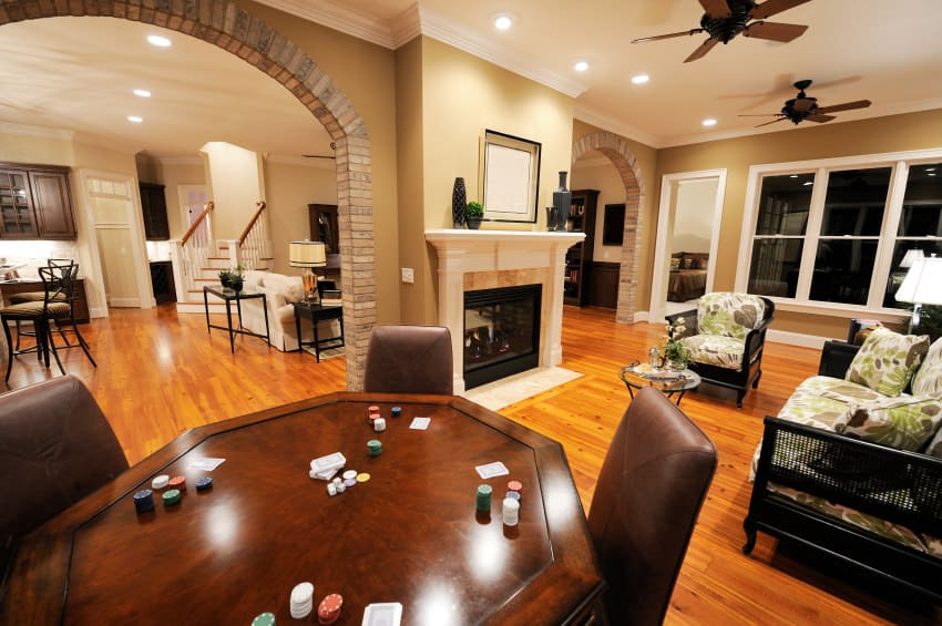 A large man cave featuring cards table and a cozy living space set on the hardwood flooring near the fireplace.