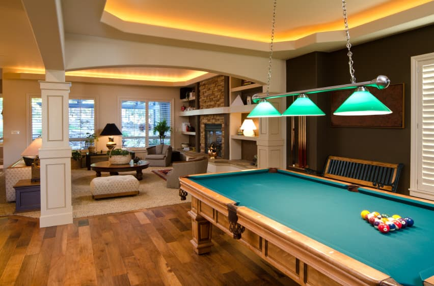 This man cave boasts a stunning ceiling with very attractive ceiling lights. There's a living space near the fireplace and a billiards pool lighted by a charming pendant lighting.