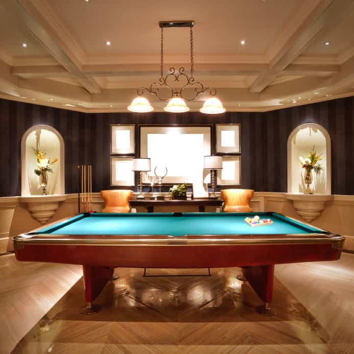 An elegant game room featuring classy walls and floors along with a stunning billiards pool lighted by a glamorous pendant lighting set on the luxurious ceiling.