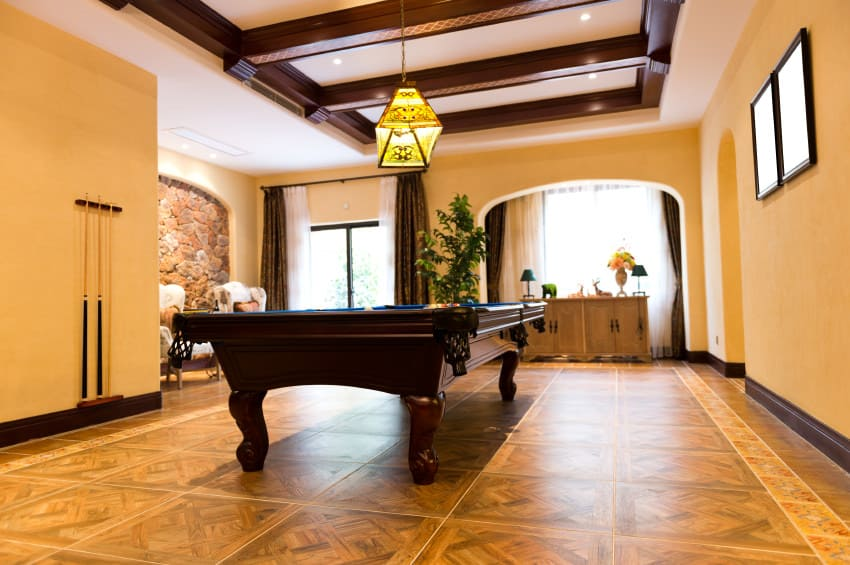 This game room boasts an elegant ceiling with beams lighted by a gorgeous pendant lighting just above the billiards pool.