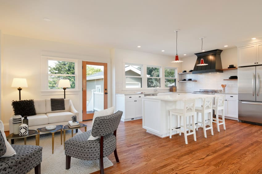 Large white great room with stylish seats set on the hardwood flooring. The kitchen boasts white center island providing space for a breakfast bar lighted by a pair of pendant lights.