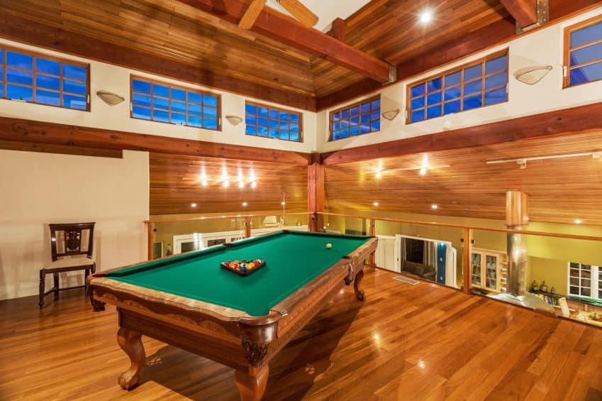 A stunning game room featuring a classic billiards pool set on the hardwood flooring that matches the ceiling. The lighting surrounding the area is absolutely gorgeous.