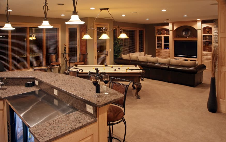 Spacious basement man cave with long dark brown leather sofa facing large screen TV set in built-in cabinetry. Behind the TV area is a small billiards table. Extending beyond that is the bar area lined with iron stools. Pendant and recessed lights illuminate the space.