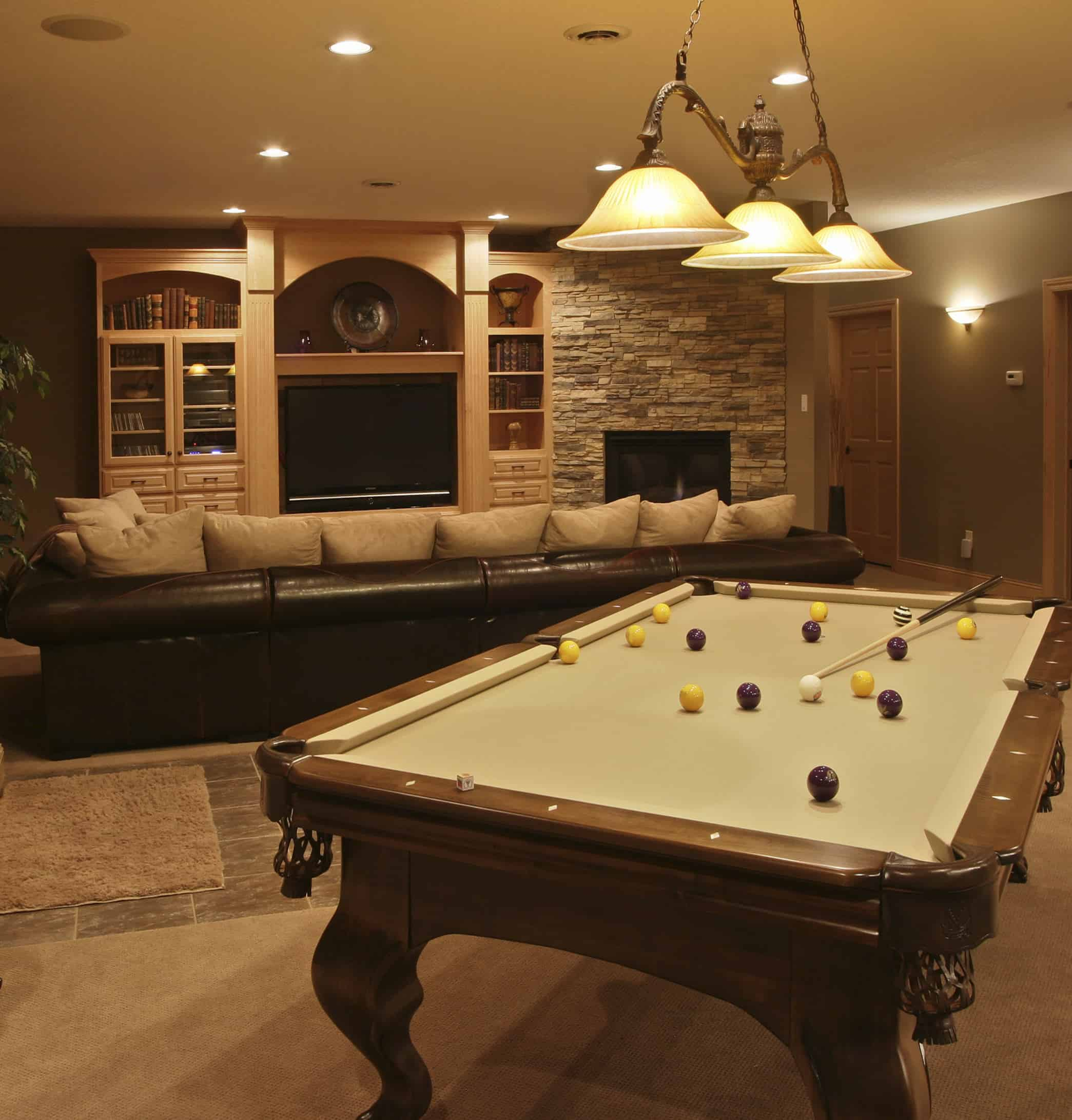 A close up look at this man cave's stylish billiards pool with white cloth and is lighted by charming pendant lighting.