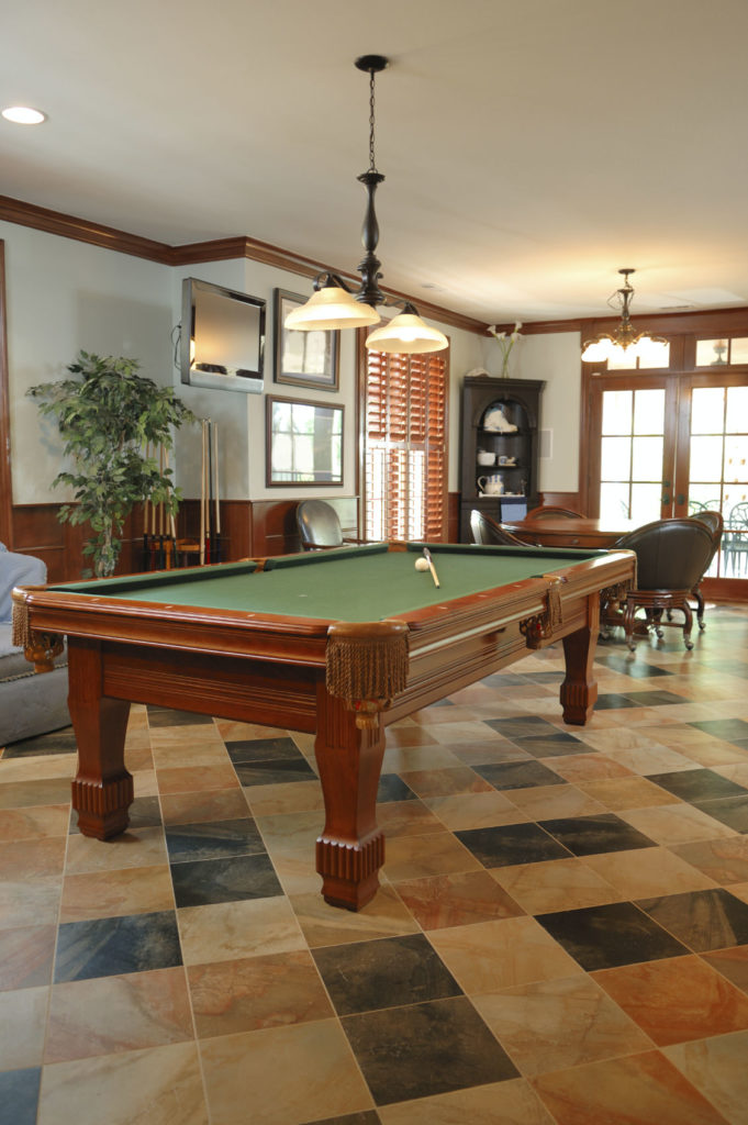 A close up look at this man cave's billiards pool set on the classy tiles flooring, lighted by a lovely pendant lighting.