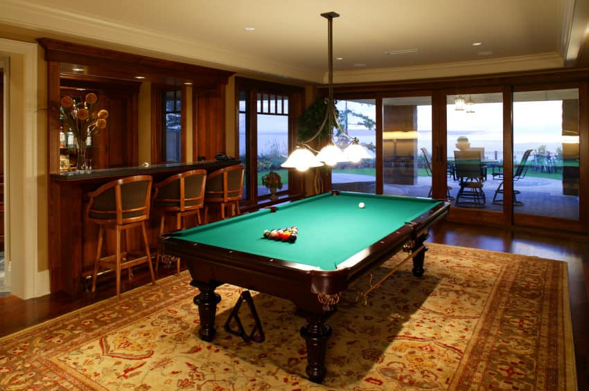 This man cave boasts a classic billiards pool set on the elegant rug on top of the hardwood flooring. The room also features a small bar area.
