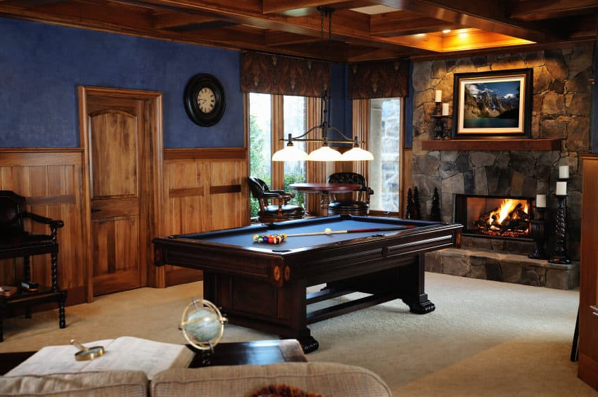 Chalet rustic style man cave with small stone faced fireplace, billiards table, small wooden round pub-style table and stools plus sofa with coffee table. This room oozes warmth with the fireplace and light beige carpeting. The centerpiece is the dark wood, blue-surface billiards table.