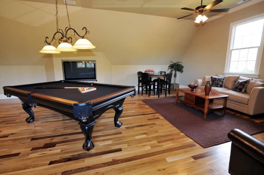 This man cave boasts a very elegant black billiards pool set on the stylish hardwood flooring and is lighted by a charming pendant lighting.