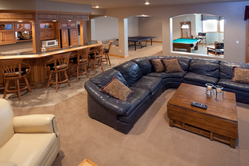 Large man cave featuring a black leather sofa set along with a large bar area. There's also a table tennis set and a billiards pool on the other side of the room.